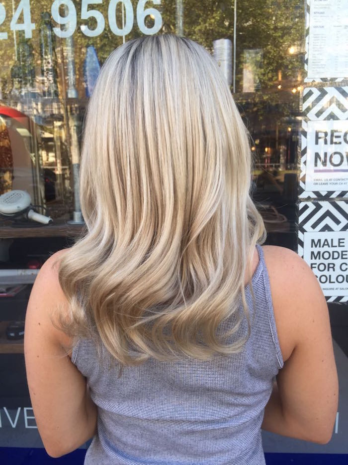 blonde highlights Brixton with soft waves on woman in front of hair salon